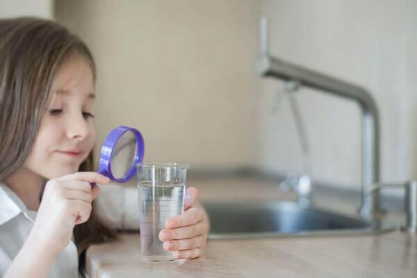 Osmose inverse : Enfant scrutant son verre d'eau