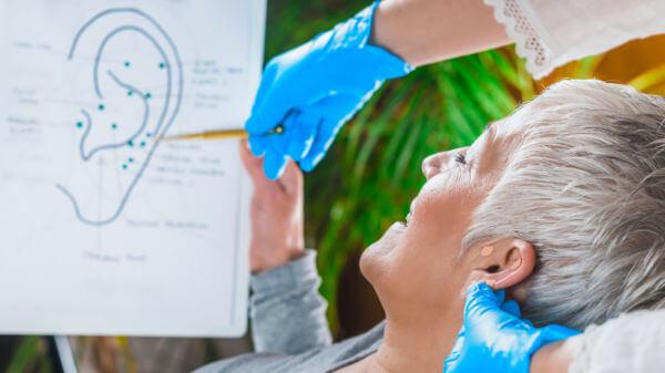 patiente apprenant les points d'auriculothérapie