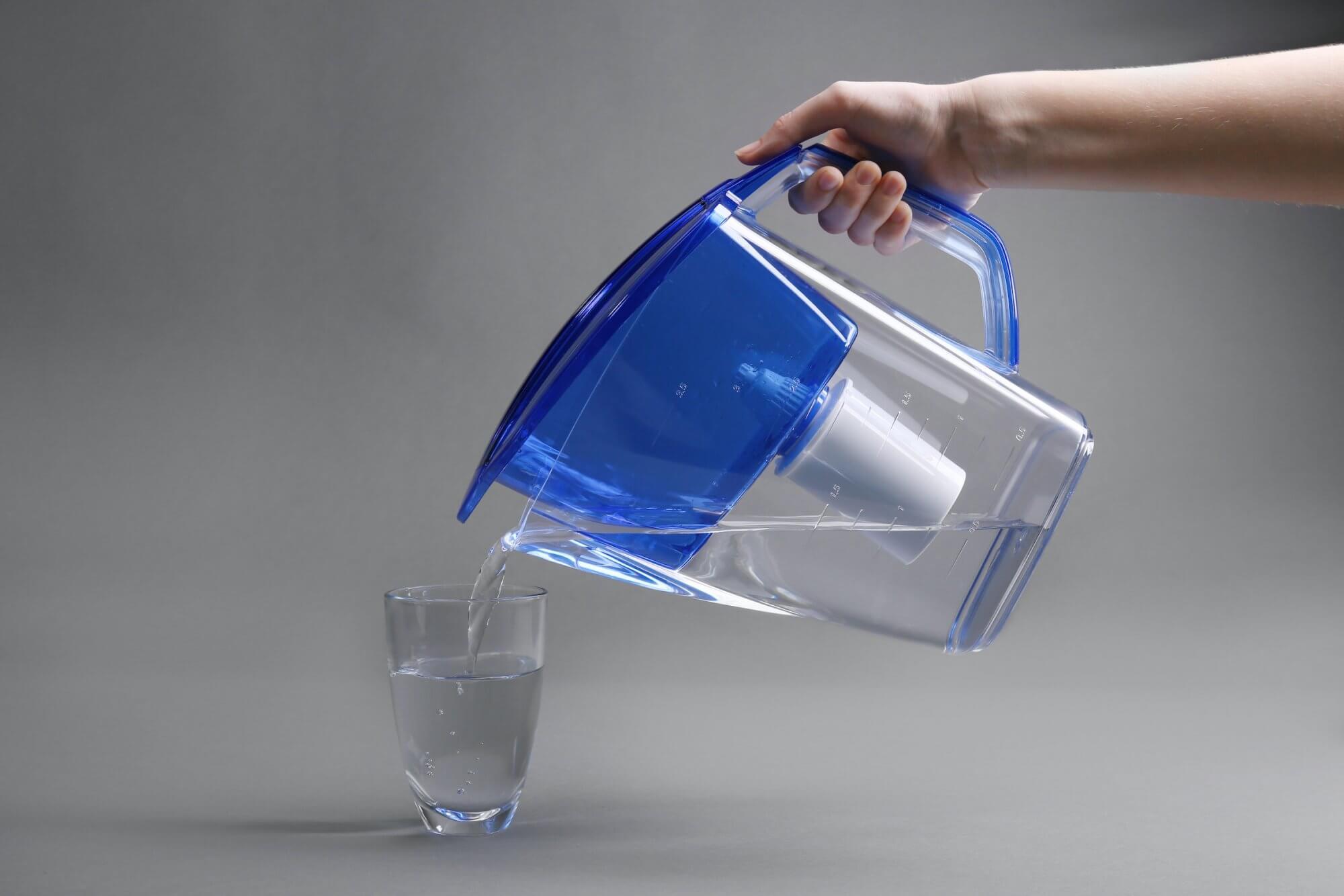 L'eau d'une carafe filtrante est versée dans un verre