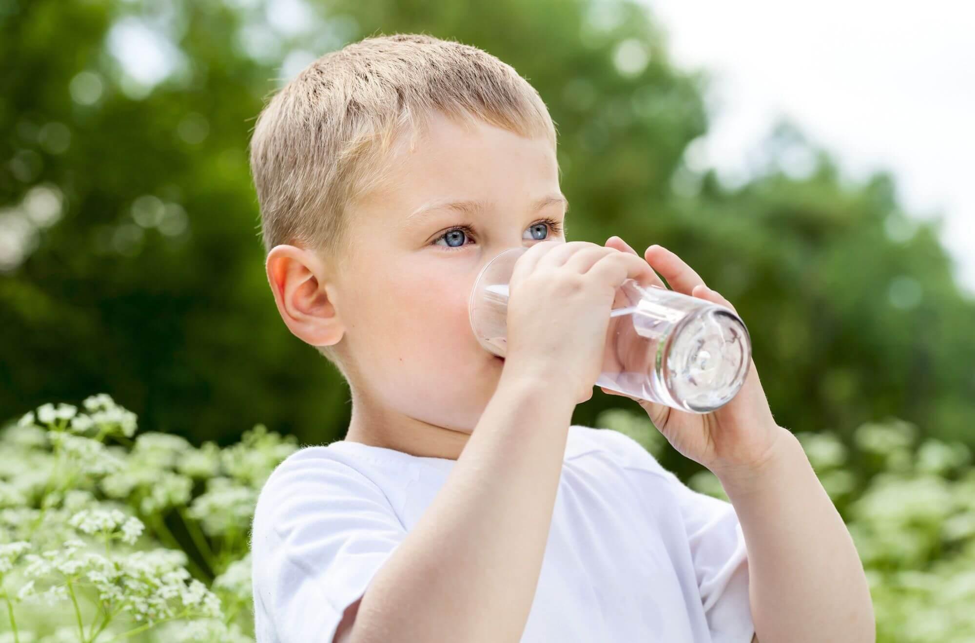 garçon buvant de l'eau dans un verre transparent