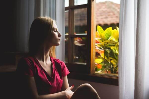 Femme qui se détend et respire profondément devant sa fenêtre ouverte