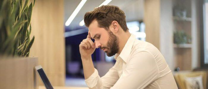 Homme assis à son bureau et se tenant la tête